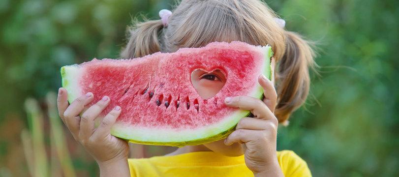 child eats a watermelon in the garden. Selective focus.