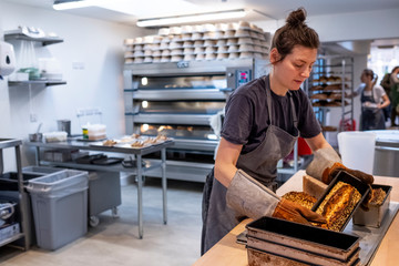 Woman wearing apron and oven gloves standing in an artisan bakery, turning out freshly baked loaves of seeded bread.