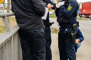 Unrecognizable German Polizei Police officers checks people at the border crossing in Kehl from France Strasbourg during crisis measures novel coronavirus