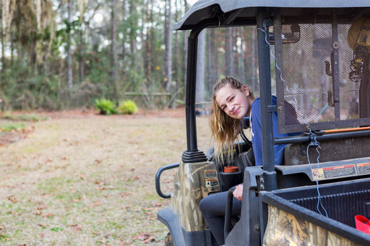 A teenage girl in an all terrain vehicle, a buggy, looking out.