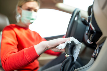 Epidemic outbreak. Woman cleaning steering wheel in the car.