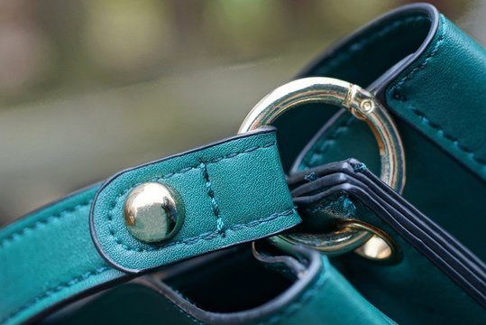 green leather harness on bag with yellow metal rivet and carabiner ring