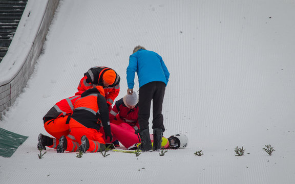 Paramedics and rescue workers helping an injured ski jumper on the bottom of the ski jump. Injured ski jumper in pain.