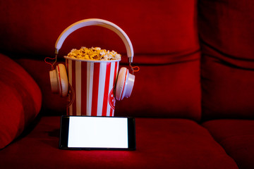 mobile phone with empty white bright screen with popcorn bucket on the red sofa. Concept of streaming TV on internet phone.