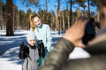 Mother taking a picture of her two children, a boy and teenage girl in snowy forest landscape.,Valle Caldrea