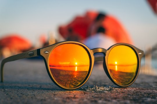 Pair of sunglasses on the beach with the reflection of the sunset