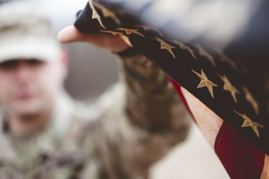 Shallow focus shot of an American soldier holding the American flag