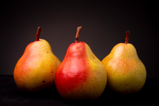 Still life of three vibrant colourful ripe yellow red Seckel pears contrasted against a dark studio background
