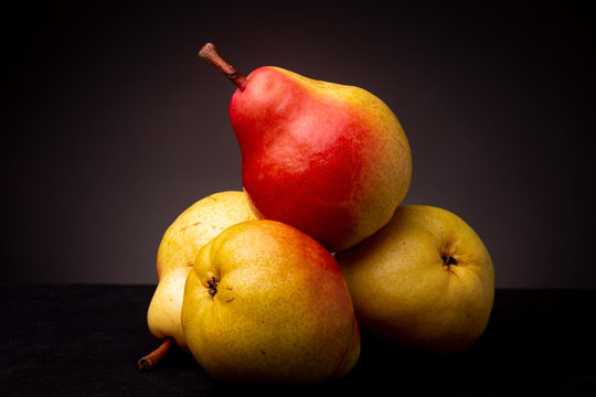 Vibrant colourful yellow red Seckel pear resting slanted on other pears on a black surface contrasted against a dark grey background