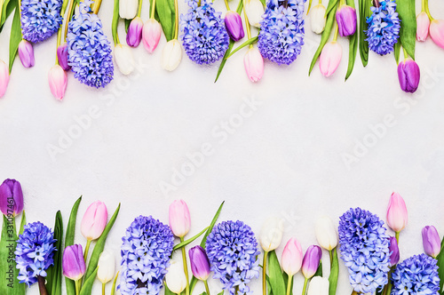 Colorful tulips and hyainths border on light background. Mothers day, Valentines Day, Birthday celebration concept. Top view, copy space