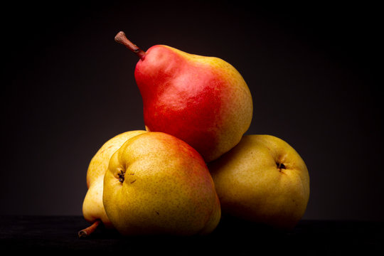 Studio closeup still life of a lot of vibrant colourful yellow red Seckel pear resting slanted on other pears on a black surface contrasted against a dark grey background