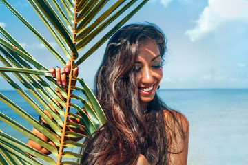 beautiful young cheerful woman on the beach with palm leaf