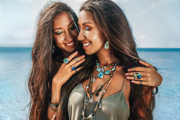 close up of two cheerful young women sisters twins on the beach