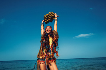 cheerful young stylish woman having fun with bunch of banans on the beach