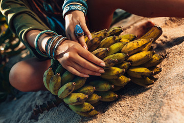 close up of woman hands with boho accessories holding a bunch of banans