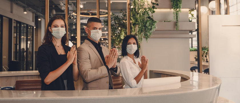 hotel receptionist wearing medical mask and show greeting with thai wai for being new greeting practice during coronavirus covid 19 pandemic, new greeting practise in coronavirus covid 19 pandemic