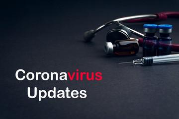 Stethoscope, Vial and Syringe with words CORONAVIRUS UPDATES on black background. Covid-19 concept...