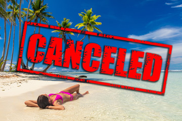 Travel vacation and flight canceled because of coronavirus travel ban. Corona virus crisis in airline and travel industry. Canceled red stamp text on beach woman relaxing lying down on holidays.