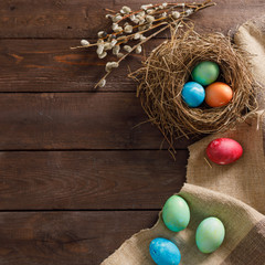 Still life of easter eggs in a bird's nest on a wooden background. Rustic. Decoration of natural. Easter celebration concept. Copy space. Flat lay. Square.