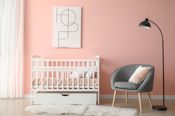Baby bed with armchair in interior of children's room