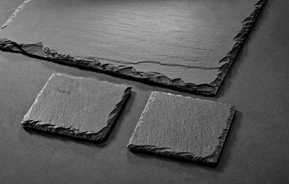 black matte slate natural stone coasters on gray background