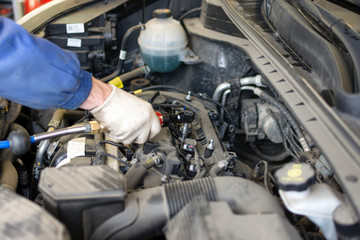 Car repair at a service station. The hands of a professional mechanic hold a tool. Spark Plug Replacement