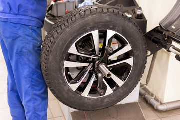 Seasonal winter tire service. Professional mechanic in car service. Car wheel on a machine for balancing. Mechanic at work.