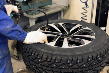 Seasonal winter tire service. Professional mechanic in a car service. A car wheel on a machine for replacing tires. A mechanic at work.