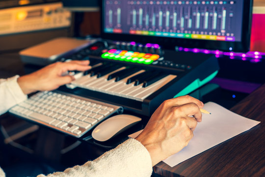 male composer hands writing lyric on paper and creating melody on midi keyboard and computer