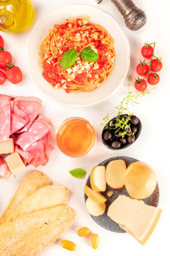 Italian food. Pasta, cheese, ham, wine, tomatoes, shot from above on a white background