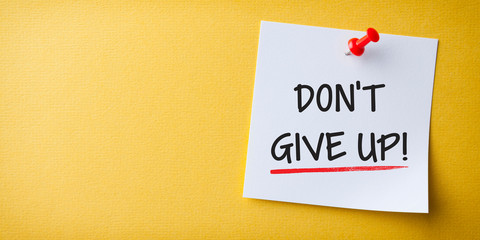 White Sticky Note With Don't Give Up And Red Push Pin On Yellow Background