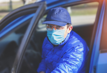 A man in a medical mask (respirator) gets out of a car during an epidemic