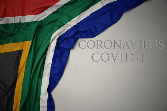 waving national flag of south africa on a gray background with text coronavirus covid-19 . concept.