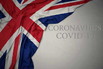 waving national flag of great britain on a gray background with text coronavirus covid-19 . concept. Fotoväggar