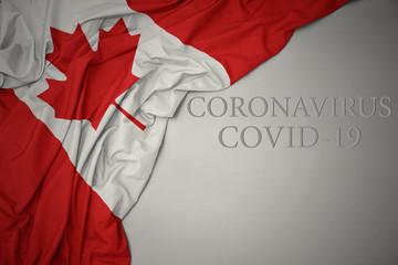 Poster Canada waving national flag of canada on a gray background with text coronavirus covid-19 . concept.