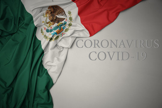 waving national flag of mexico on a gray background with text coronavirus covid-19 . concept.