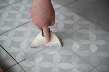 Tiler laying the ceramic tile on the floor. Professional worker makes renovation. Construction. Hands of the tiler. Home renovation and building new house