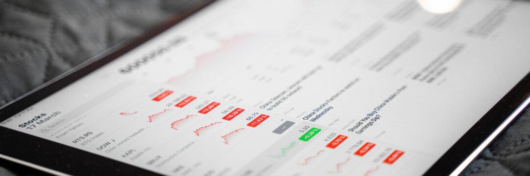 Tablet with negative red stock market information. Global market crash. 2020 defolt