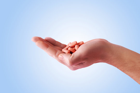 Men holding hiv therapy pills on pink background.