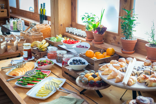 BREAKFAST BUFFET TABLE FILLED WITH ASSORTED FOODS