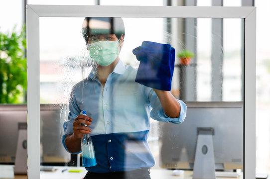 Employee disinfecting office equipment.