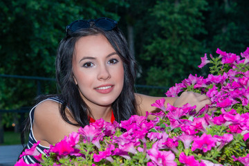 Young woman standing near with beautiful flowering petunias outdoors