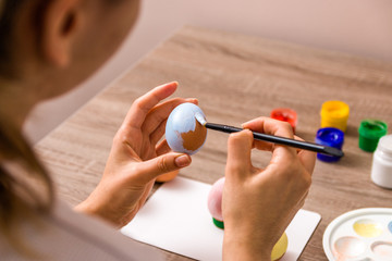 easter mood. close up young woman hands painting easter eggs with brush and gouache in pastel...