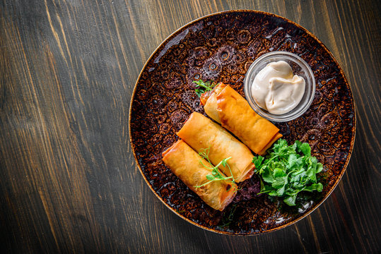 Spring rolls with shrimp and sause in plate on wooden table background