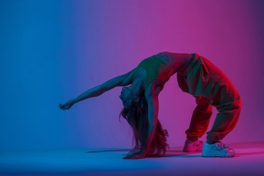 Modern young woman in trendy sportwear doing yoga in the room with pink -blue color in disco style. Professional girl is training in the studio with an amazing stylish colorful light.Healthy lifestyle