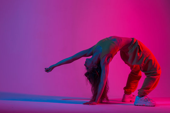 Athletic young woman in fashion sport suit doing yoga exercises in a room with red color in disco style. Girl yoga instructor is doing fitness in the studio with an amazing multi-colored light.