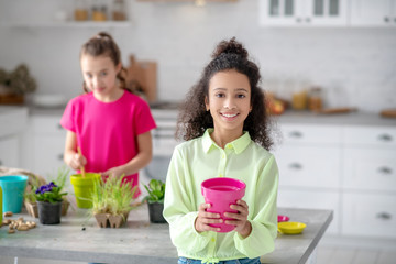 Smiling african american girl holding a pot in her hands