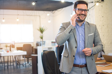 Handsome businessman talking on mobile phone in office