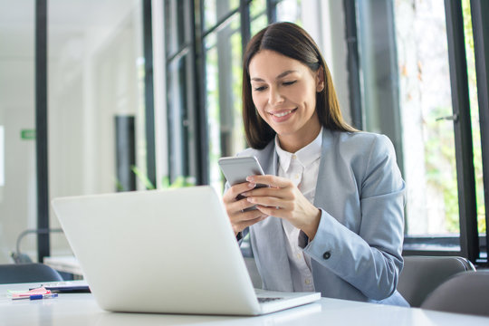 Beautiful young business woman using phone in office