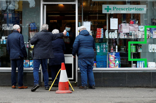 Customers queue outside a pharmacy in Belfast